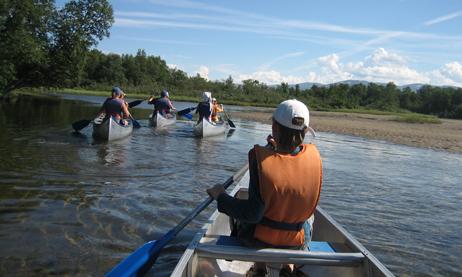 Scouter med flytvästar paddlar kanot